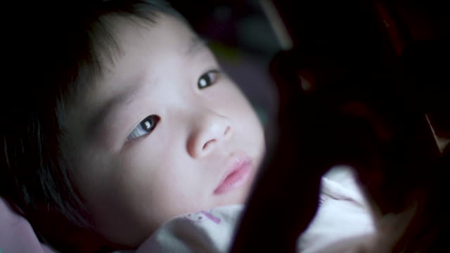 Close-Up Of Baby Girl Using Smartphone At Night