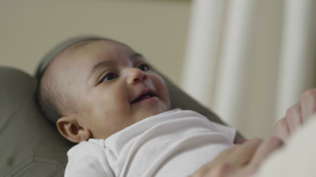 close-up of baby smiling as her father plays with her feet - baby human age stock videos and b-roll footage