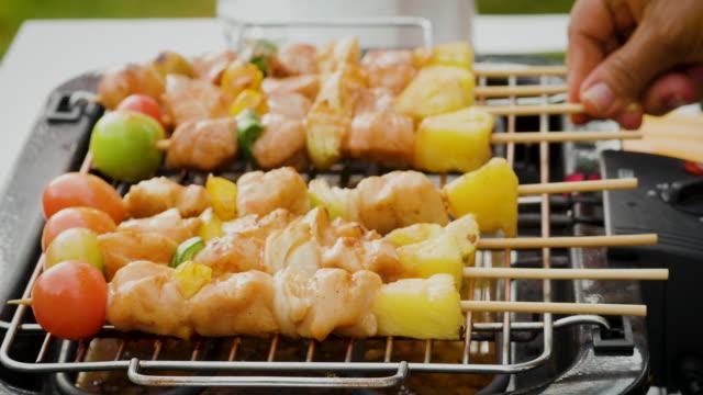 Close-up van barbecue met varkensvlees en groenten op vlammende grill