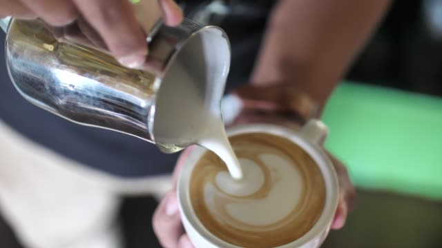 close-up of barista adding foamy milk into a cup of coffee - making stock videos & royalty-free footage