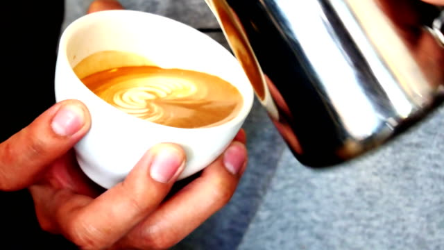 closeup of barista making latte art in cafe. - froth art stock videos and b-roll footage