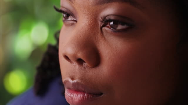 closeup of beautiful african american woman with gentle smile in outdoor setting - まつげ点の映像素材/bロール