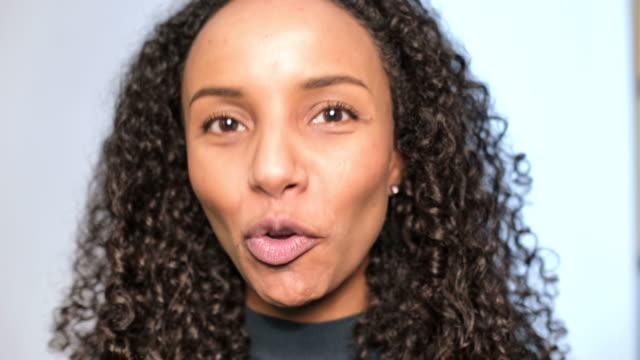 vídeos de stock, filmes e b-roll de close-up da mulher africana bonita que fala - fundo branco