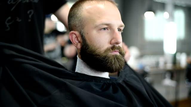 stockvideo's en b-roll-footage met close-up van de mooie aantrekkelijke volwassen man met baard in een kapper - kammen