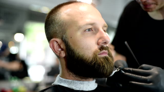 close-up of beautiful attractive adult man with beard in a barber shop - cutting hair stock videos and b-roll footage
