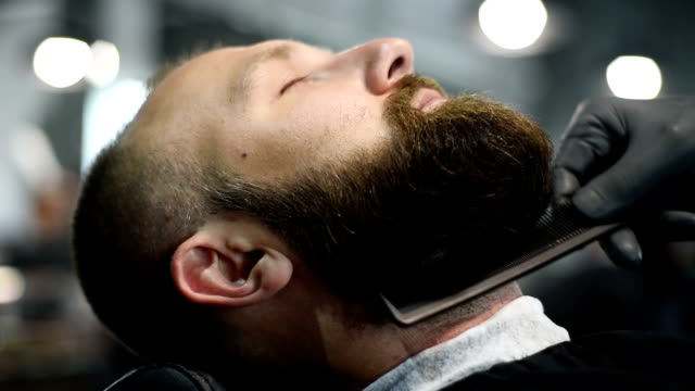Close-up of beautiful attractive adult man with beard in a barber shop