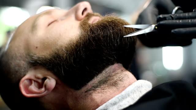 schöne attraktive erwachsene mann mit bart in einen friseurladen in nahaufnahme - gartengerät stock-videos und b-roll-filmmaterial
