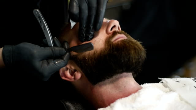 close-up of beautiful attractive adult man with beard in a barber shop - barba peluria del viso video stock e b–roll