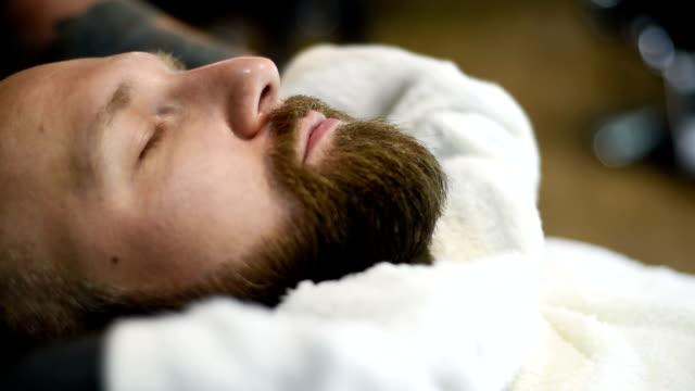Schöne attraktive Erwachsene Mann mit Bart in einen Friseurladen in Nahaufnahme