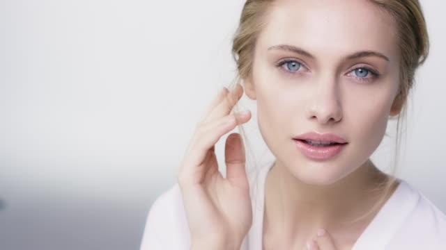 nahaufnahme der schöne schüchterne frau, ihr gesicht zu berühren - kosmetik stock-videos und b-roll-filmmaterial
