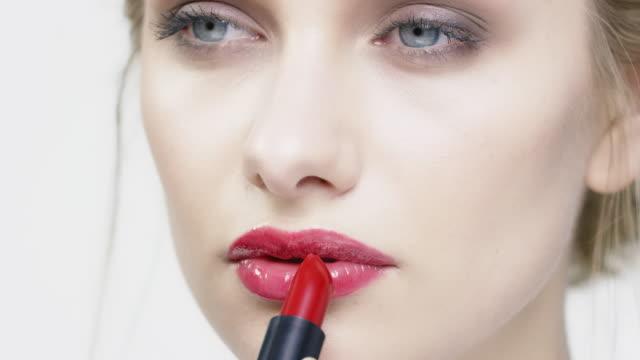vídeos de stock, filmes e b-roll de close-up da mulher bonita, aplicar o batom vermelho - aplicando