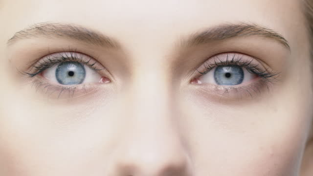 Close-up of beautiful woman opening her blue eyes