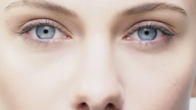 vídeos de stock e filmes b-roll de close-up of beautiful young woman with blue eyes - fade in