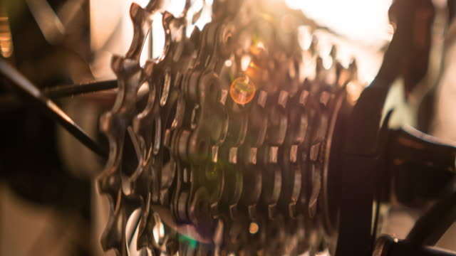 Close-up of bicycle gear and chain in motion at sunrise