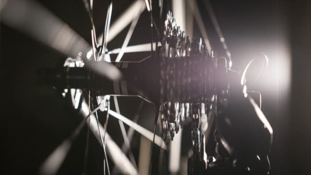 close-up of bicycle gear and chain on black background, illuminated by artificial light - triathlon stock videos & royalty-free footage