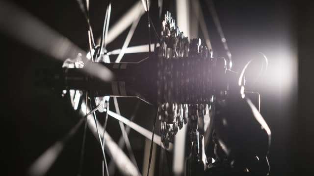 Close-up of bicycle gear and chain on black background, illuminated by artificial light
