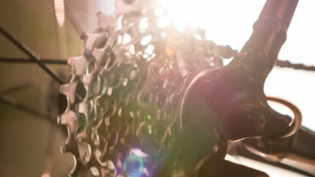 close-up of bicycle wheel spoke, gear and chain in motion with lens flare - wheel stock videos & royalty-free footage