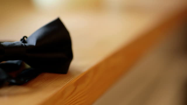 Closeup Of Black Bowtie On Wooden Table