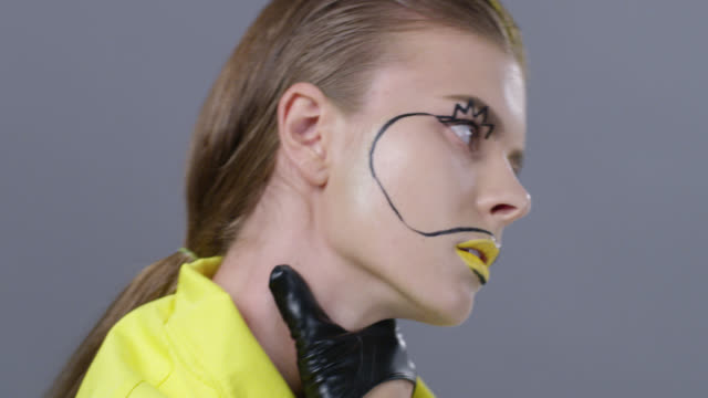 close-up of blond fashion model in a bright stage make-up and black leather gloves strangles herself. fashion video. - out of breath stock videos and b-roll footage