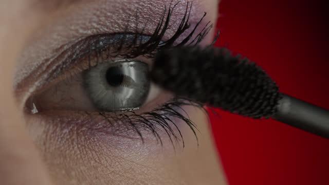 nahaufnahme von blauen augen und wimpern eines mädchens, das mascara aufwendet. - wimper stock-videos und b-roll-filmmaterial