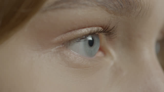close-up of blue eyes of a young girl. - blue eyes stock videos & royalty-free footage