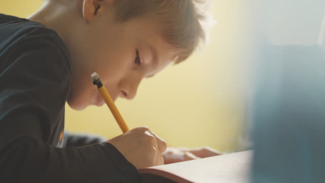 close-up of boy (10-11) doing homework at desk - solo un bambino maschio video stock e b–roll