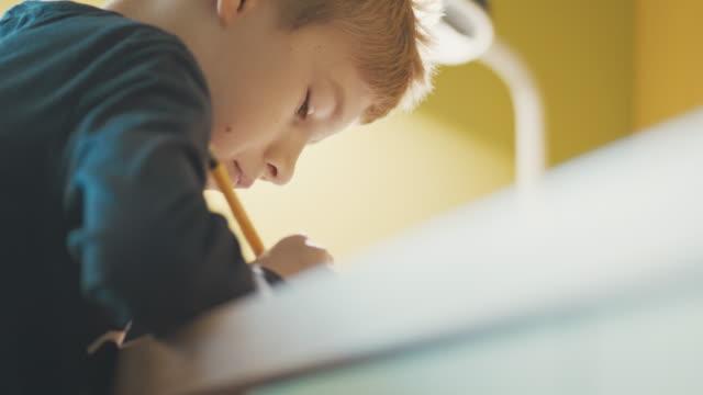 Nahaufnahme eines jungen (10-11) Hausaufgaben am Schreibtisch