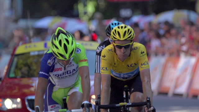 closeup of bradley wiggins yellow jersey followed by chris froome crossing finish line on stage 16 of 2012 tour de france - ツール・ド・フランス点の映像素材/bロール