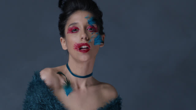 close-up of brunette fashion model in bright stage make-up and feathers, that moves and shows facial expressions. fashion video. - greasepaint stock videos and b-roll footage