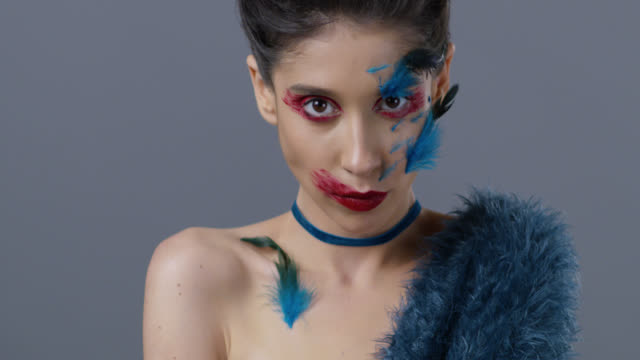 close-up of brunette fashion model in bright stage make-up and feathers, that shows facial expressions. fashion video. - body paint stock videos & royalty-free footage