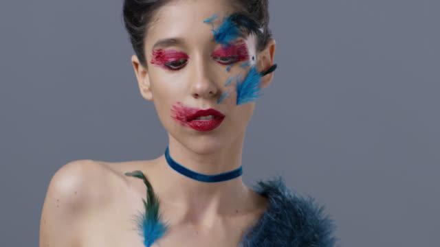 vídeos de stock, filmes e b-roll de close-up da modelo morena moda em maquiagem de palco brilhante e penas, que mostra expressões faciais. vídeo de moda. - maquiagem para teatro