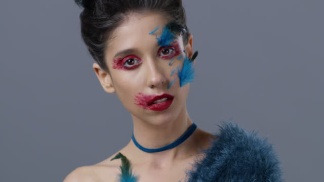nahaufnahme der brünette mode-modell in hellen bühne make-up und federn, zeigt, dass mimik. mode-video. - halsreif stock-videos und b-roll-filmmaterial