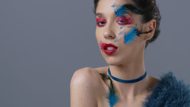 close-up of brunette fashion model in bright stage make-up and feathers, that shows facial expressions, hissing. fashion video. - profilo vista laterale video stock e b–roll