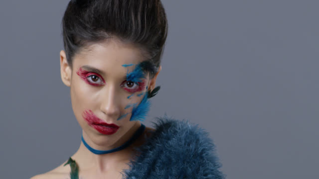 Close-up of brunette fashion model in bright stage make-up and feathers, that shows facial expressions. Fashion Video.