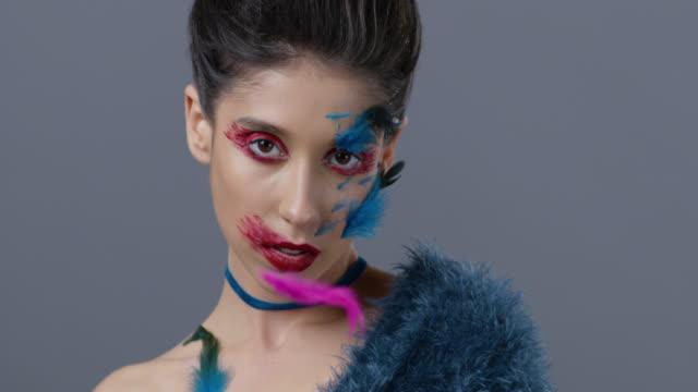 vidéos et rushes de gros plan du mannequin brune en maquillage de scène lumineux et plumes, qui montre les expressions faciales. mode vidéo. - rouge à lèvres rouge