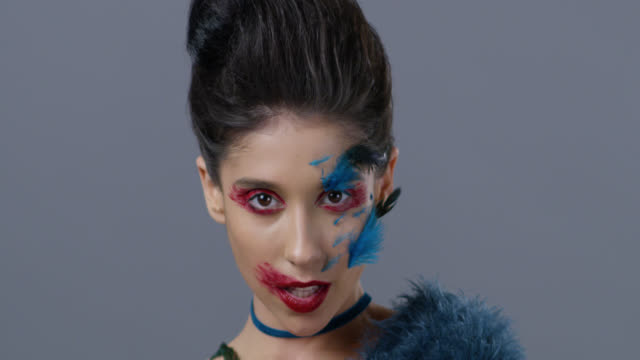 Close-up of brunette fashion model in bright stage make-up and feathers, that moves and shows facial expressions. Fashion Video.