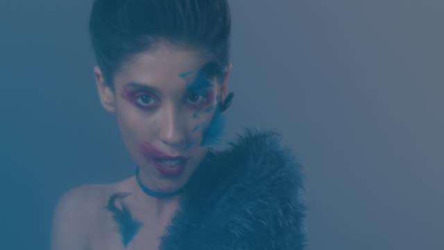vidéos et rushes de gros plan du mannequin brune en maquillage de scène lumineux et plumes, qui montre les expressions faciales, s'embrasser. plumes tombent. mode vidéo. - rouge à lèvres rouge