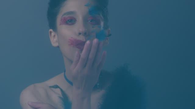 Nahaufnahme der Brünette Mode-Modell in hellen Bühne Make-up und Federn, zeigt, dass Mimik, küssen. Federn fallen nach unten. Mode-Video.