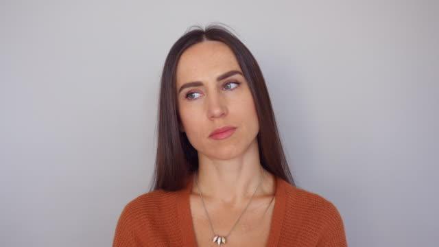 vídeos de stock, filmes e b-roll de close-up de mulher morena fazendo expressões faciais diferentes, mostrando o olhar aborrecido - expressão facial