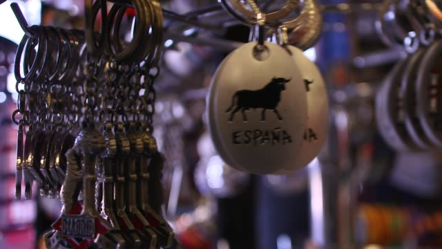 vídeos y material grabado en eventos de stock de close-up of bull key rings on display in shop in slow motion, madrid, spain - recuerdos