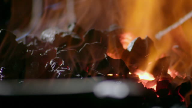 close-up of burning coals in a crackling fire. - 石炭点の映像素材/bロール
