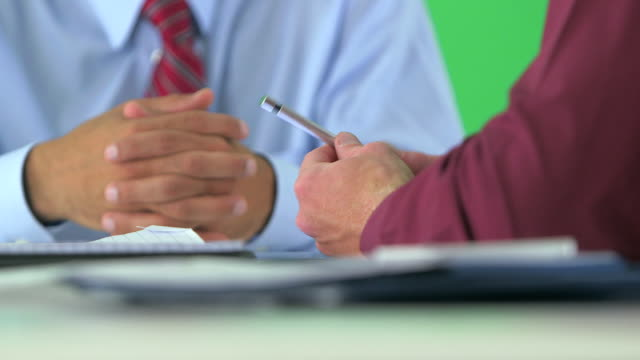 close-up of business hands holding pen on greenscreen