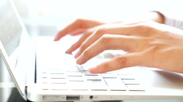 Primo piano di donna d'affari digitando sulla tastiera del computer portatile mano