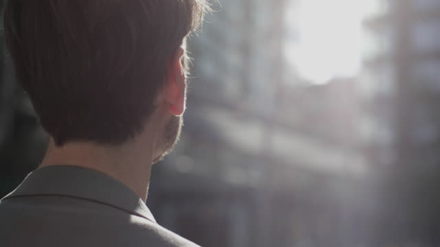 closeup of businessman looking out to city - men stock-videos und b-roll-filmmaterial