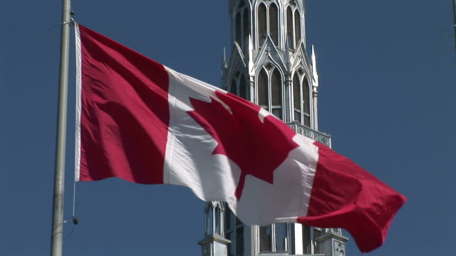 stockvideo's en b-roll-footage met close-up of canadian flag flapping in front of parliament of ottawa canada - senaat verenigde staten