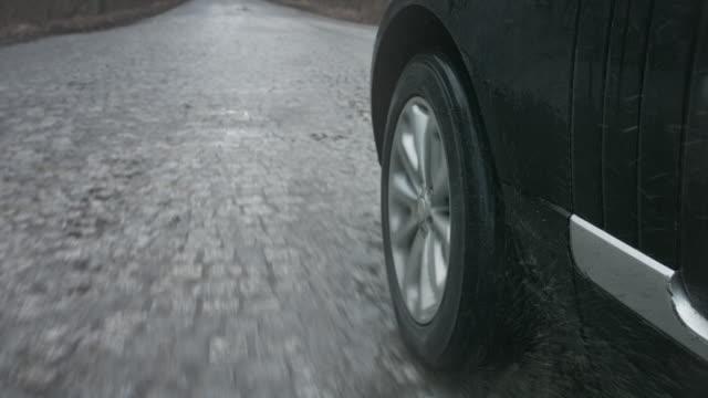 close -up の 車ホイールアゲインスト roud - 立ち去る点の映像素材/bロール