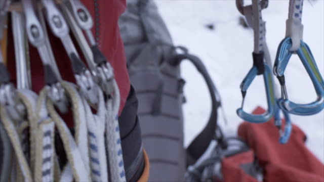 vídeos de stock e filmes b-roll de close-up of carabiners on a climbing harness belt on an ice climber in the mountains. - slow motion - equipamento de alpinismo