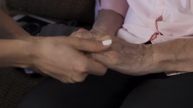 vídeos y material grabado en eventos de stock de primer plano de enfermera cariñosa que se da de la mano de la mujer mayor en casa - rezar