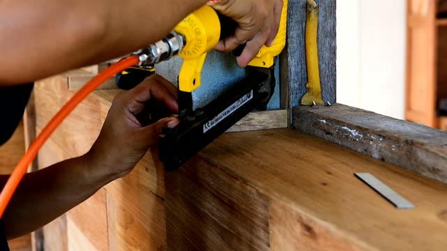 closeup of carpenter shoot nail gun in workshop