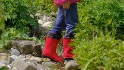 Close-up of child in red rubber boots walking through garden